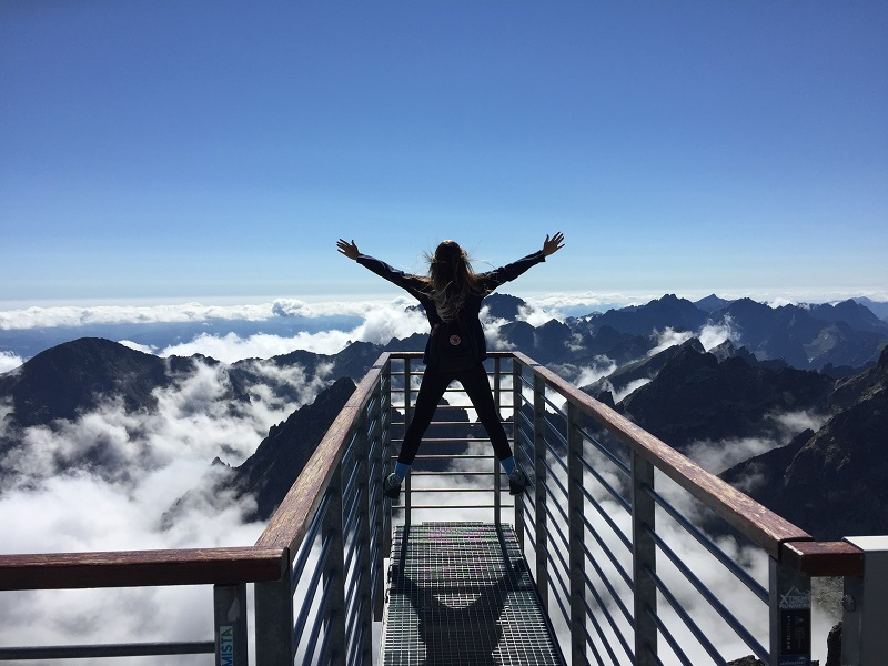 person-standing-on-hand-rails-with-arms-wide-open-facing-the-725255